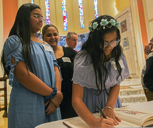 Catechumen Amanda Cruz, from Good Shepherd Church in Miami, signs the Book of the Elect after her sister, Abigail Cruz, as their mother and sponsor, DaMarie Gonzalez, looks on. They were among about 550 catechumens who took part in one of the two Rite of Election ceremonies held March 1, 2020, at St. Mary Cathedral.