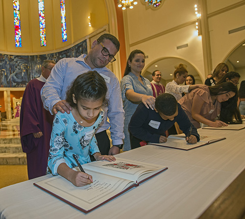 Catechumen Aislinn Izquierdo signs the Book of the Elect as her sponsor, Christopher Munoz, looks on. She was among about 550 catechumens who took part in one of the two Rite of Election ceremonies held March 1, 2020, at St. Mary Cathedral.