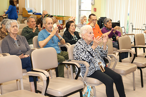 Clients of Centro Oeste Adult Day Care Center in Davie, run by Catholic Charities of the Archdiocese of Miami, join in prayer as they begin a day of activities in this file photo from June 2019. In response to the coronavirus threat, Catholic Charities will begin home delivery of meals to clients of its elderly services and congregate meals programs.