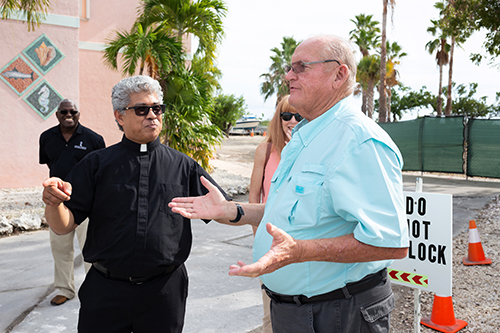 At St. Peter Parish in Big Pine Key, Father Jets Medina, parochial administrator, listens to Marty Mara, chairman of the parish building committee, which is overseeing the construction of a new church and rectory to replace the ones damaged by Hurricane Irma in 2017.