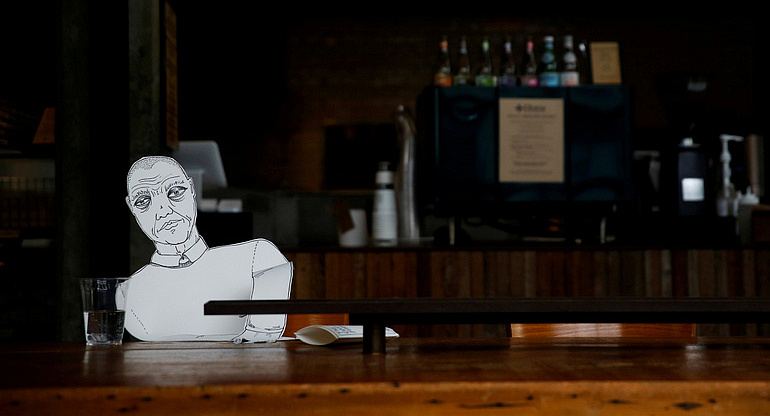 A paper cutout of a person sits at an empty table at a bagel cafe during the coronavirus pandemic in Seattle March 27, 2020. Outreach efforts by Catholic agencies continue in large part during the virus-mandated restrictions. (CNS photo/Lindsey Wasson, Reuters) See SERVICE-WORKAROUNDS March 31, 2020.