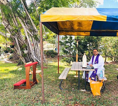 In late March, Father Julio De Jesus, pastor of St. Benedict in Hialeah, poses in front of the outdoor confessional space he improvised on the parish grounds. Note the social distance.