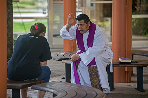 Father Antonio Tupiza hears a confession in the kiosk area of St. Rose of Lima Church, Miami Shores, March 28, 2020. Priests in the archdiocese continue to hear confessions by appointment while following social distancing measures to protect themselves and parishioners against COVID-19.