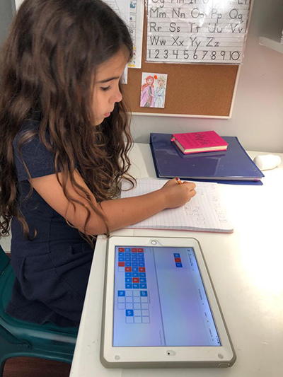Ava Piñero, 7, works on her spelling assignment at her home desk.