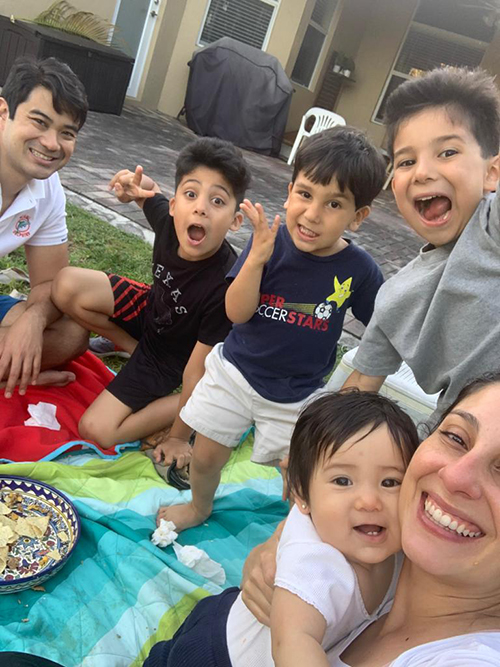 """The Caballero family enjoys creating memories with a nacho picnic during quarantine. """"That was awesome because it was a big bowl of nachos and I didn't even do plates. So the clean up was the one plate, some cups and washing the blanket,"""" said Odalys Caballero. """"The kids had an awesome memory of how fun it was to have dad around and a restful, fun and different dinner."""" From left: Matthew Caballero, Samson, 8; Jorge, 6; Mateo, 3; Serafina, 10 months; and Odalys Caballero."""
