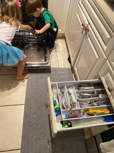 Angela Amaro, 5, and Jorge, 2, empty the dishwasher and store the utensils in the drawer.