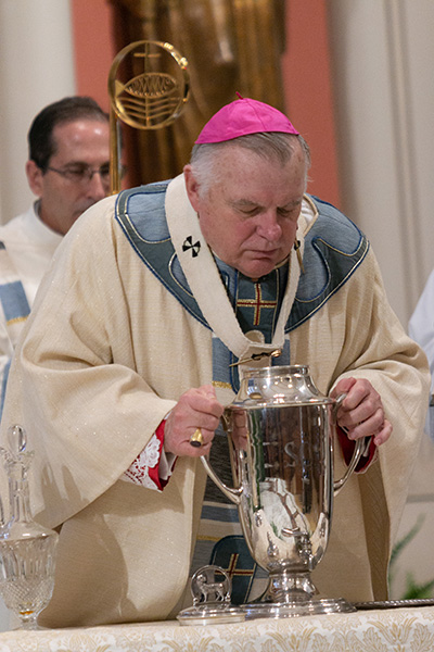 Archbishop Thomas Wenski blows into the oil of chrism,  consecrating it for use in ordinations of bishops and priests and consecrations of churches and altars.