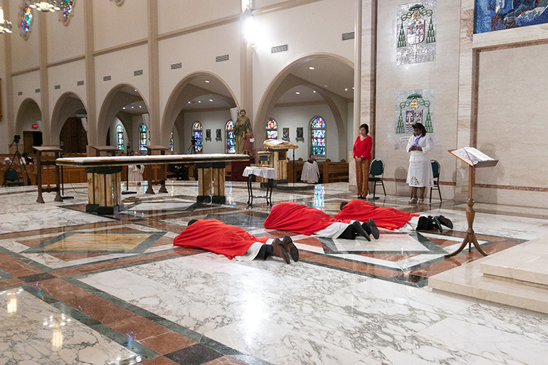 Archbishop Thomas Wenski, center, accompanied by two deacons, lies prostrate on the sanctuary of St. Mary Cathedral in Miami at the start of the Good Friday liturgy of the Passion of the Lord, April 10, 2020. Due to the coronavirus pandemic, only Missionaries of Charity and a few cathedral staff were present. The Mass was livestreamed on the Archdiocese of Miami's Facebook and YouTube pages.