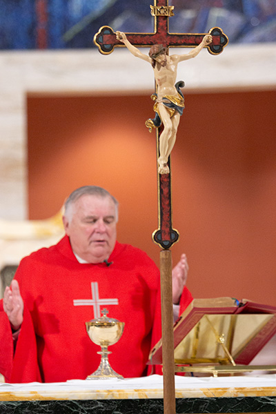 Archbishop Thomas Wenski prays the Our Father before distributing Communion during the Good Friday liturgy of the Passion of the Lord celebrated in a nearly empty St. Mary Cathedral, April 10, 2020.