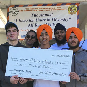 "Various youth from the town of Southwest Ranches hold up the check they helped fundraise during the second annual ""A Race for Unity in Diversity"" 5K Run/Walk on February 29. Left to right is Nikolas Garcia, Muskan Singh, Pavitpaul Singh, Ramanpreet Singh, and Parneet Singh.