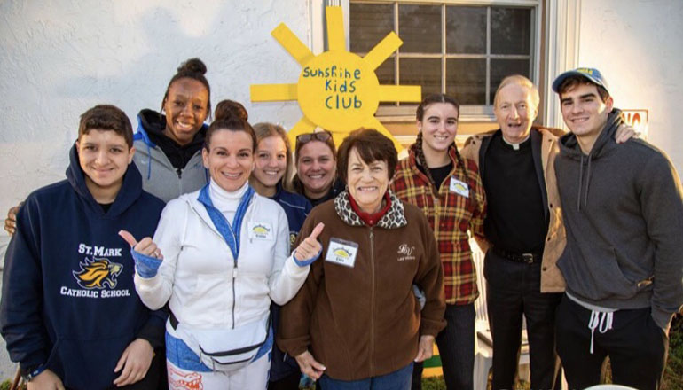 Members of the Sunshine Kids Club from Southwest Ranches pose for a photo, along with Father Patrick O'Neil archdiocesan director of Ecumenical and Interfaith Relations, who came out to support the effort.