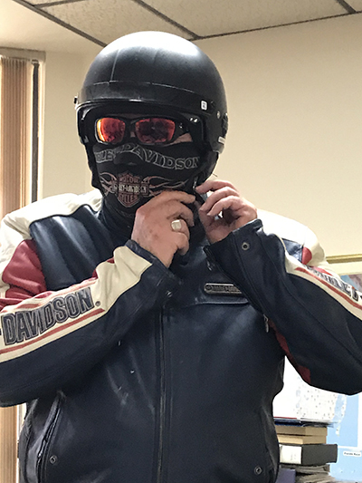 "Archbishop Thomas Wenski puts on his motorcycle mask and gear. A ride once a month, outside the city, he said, helps me de-stress and ""clear the cobwebs"" from his mind."