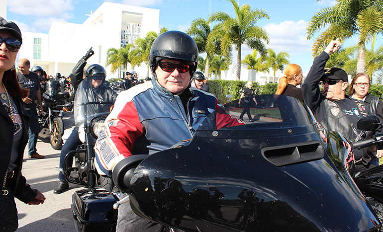 With Doral's Our Lady of Guadalupe Church in the background, Archbishop Thomas Wenski prepares to take off for Peterson's Harley Davidson during his annual Motorcycle Ride to raise funds for St. Luke's Center, Feb. 23, 2020.