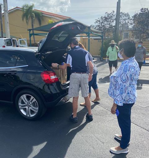 St. Rose of Lima volunteers take food donations out of a fellow parishioner's car during the food collection event April 29, 2020. School families and parish volunteers restocked neighboring St. Martha Parish's Food Pantry thanks to donations of nonperishable foods from their fellow parishioners.