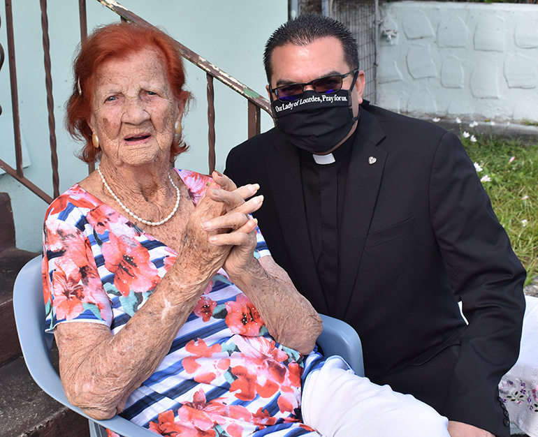 Father Javier Barreto of Little Flower Church in Hollywood poses with Stella Waite during her 105th birthday party.