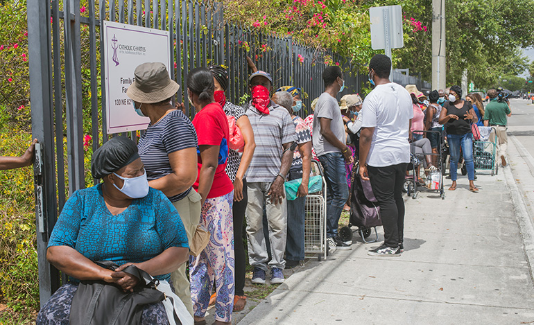 People line up outside Notre Dame d'Haiti Church in Little Haiti to receive donated food. Archbishop Thomas Wenski helped Father Reginald Jean-Mary, Notre Dame d'Haiti's pastor, hand out food at the church May 23, 2020.