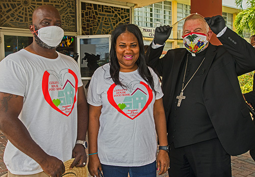 Arthur and Laverne Spicer, founders of Curley's House food bank, pose for a photo with Archbishop Thomas Wenski. Curley's House sponsored the food distribution May 23, 2020 where the archbishop helped Father Reginald Jean-Mary, Notre Dame d'Haiti pastor hand out food.