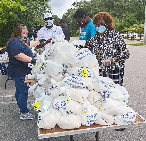 Volunteers prepare the bags of food to be given away at Notre Dame d'Haiti Church May 23, 2020. Archbishop Thomas Wenski helped Father Reginald Jean-Mary, Notre Dame d'Haiti pastor, hand out food at the church.