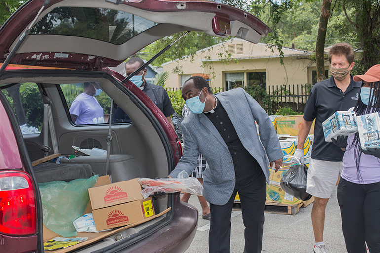 Father Reginald Jean-Mary, Notre Dame d'Haiti's pastor, places a package of fish into an SUV during the May 23, 2020 distribution hosted by his Miami church. Archbishop Thomas Wenski also helped hand out food.