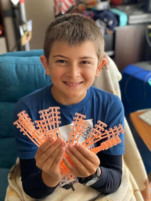 Dakotah Herald shows some of the plastic straps he produced via 3D printer to relieve ear pressure from face masks.