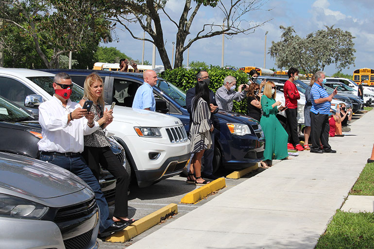 With COVID-19 safety measures in effect, parents, families and friends of Archbishop Coleman Carroll High graduates were requested to wait by their cars, or behind the school's sidewalk, as they watched the commencement ceremony May 30, 2020.