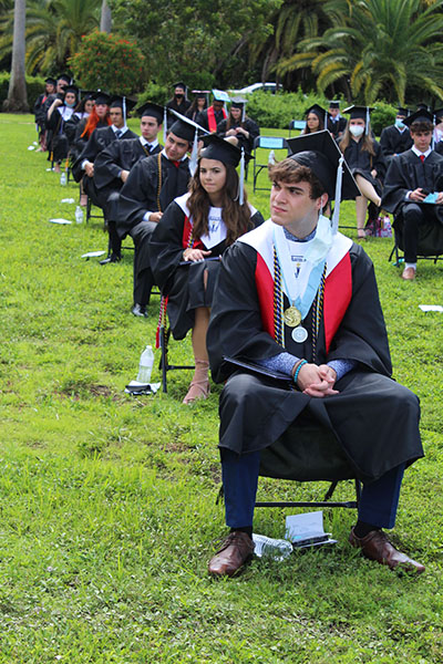 Dressed in cap and gown, and evenly spaced out, Archbishop Coleman Carroll High's graduating class of 2020 listen to remarks during their outdoor commencement ceremony held May 30, 2020 on school grounds.