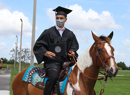 Arriving and departing by horseback, graduating senior Yancarlos Guerra from Archbishop Coleman Carroll High proudly displays his diploma after outdoor commencement ceremonies held on school grounds on May 30, 2020.