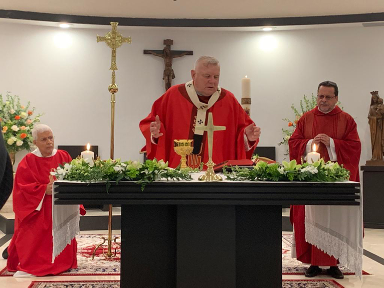 Archbishop Thomas Wenski celebrates Mass in the chapel of Mother of Christ Church in Miami, where he consecrated the new altar during the vigil Mass May 30, 2020. At right is Mother of Christ's administrator, Father Jorge Carvajal-Nino.