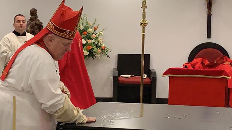 Archbishop Thomas Wenski uses oil to anoint the new altar in the chapel of Mother of Christ Church, Miami, during the vigil Mass and consecration ceremony May 30, 2020.