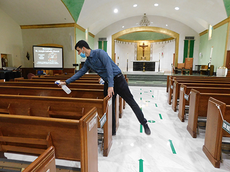 """At the conclusion of Mass, ushers at St. Joseph Church, Miami Beach, disinfect the church with the products indicated by the """"new normal"""" for the reopening of churches."""