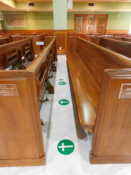 At St. Joseph Church, Miami Beach, green crosses on the floor indicate the places in the pews where people are allowed to sit, in keeping with the norms established for the re-opening of churches.