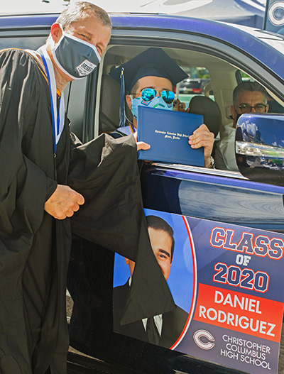 Christopher Columbus High School's president, Thomas Kruczek, gives a diploma to graduate Daniel Rodriguez. Because of the pandemic, the Miami school celebrated its graduation at the Homestead Miami Speedway June 20, 2020.
