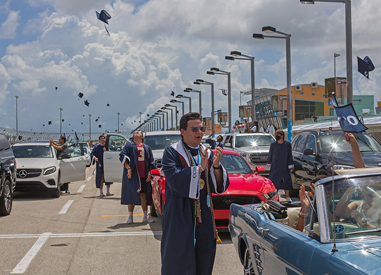 Christopher Columbus High School graduate Marcel Van Hemert applauds as classmates toss their caps into the air at the end of the ceremony. Because of the pandemic, the Miami school celebrated its graduation at the Homestead Miami Speedway June 20, 2020.