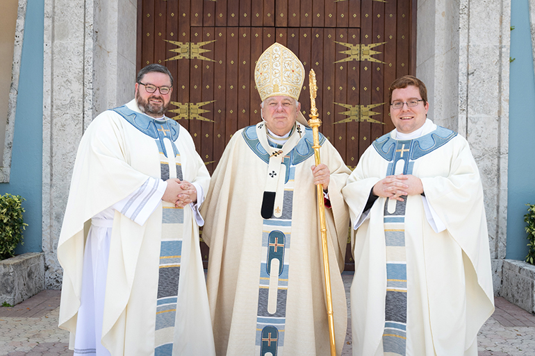 Newly ordained Father Ryan Saunders, left, and Father Andrew Tomonto, right, pose for a photo with Archbishop Thomas Wenski after the ceremony. 