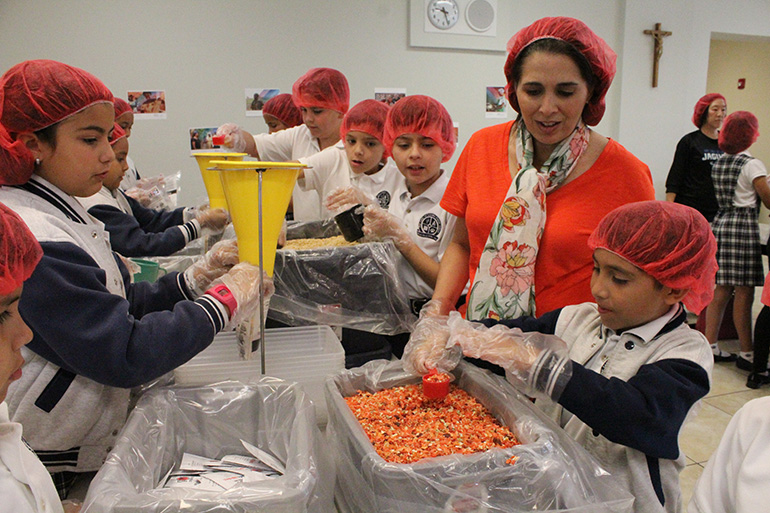 """In this file photo from 2017, Our Lady of Lourdes School's third-grade teacher, Ana-Yvette De Atienza, supervises her students as they prepare meal bags for the hungry in Burkina Faso, Africa. The Supreme Court ruled July 8, 2020 that """"that educating young people in their faith, inculcating its teachings, and training them to live their faith are responsibilities that lie at the very core of the mission of a private religious school."""""""