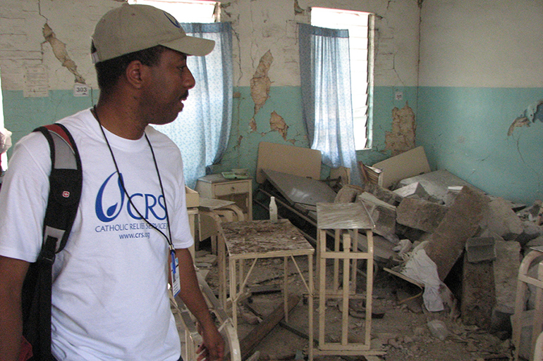 A Catholic Relief Services worker looks at the remains of a hospital in Haiti in this file photo from April 2018. Relief agencies are worried that the country's frail health system won't be able to cope with an upsurge in COVID-19 cases. There is also concern that the number of cases and deaths being reported in the country do not accurately reflect reality.
