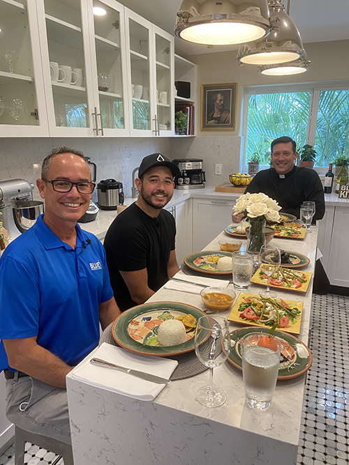 Father Richard Vigoa, rear, shares lunch with Jorge Rodriguez, left, and his son, Danny Rodriguez, during the filming of a June 4, 2020 episode of Bless This Kitchen at St. Augustine Church in Coral Gables. Danny Rodriguez co-founded BLUE Missions with his sister; their father now serves as chief growth officer.