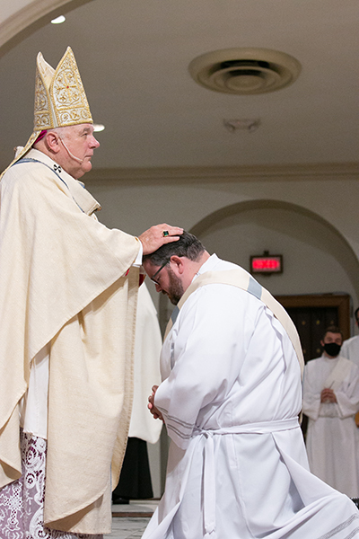 """Archbishop Thomas Wenski lays hands on Deacon Ryan Saunders, ordaining him """"a priest forever.""""  Archbishop Thomas Wenski ordained two South Florida natives to the priesthood for the Archdiocese of Miami June 27, 2020. The ceremony had been postponed from May due to the COVID-19 outbreak, and was still punctuated by mask-wearing and social distancing among the limited number of both faithful and priests in attendance."""