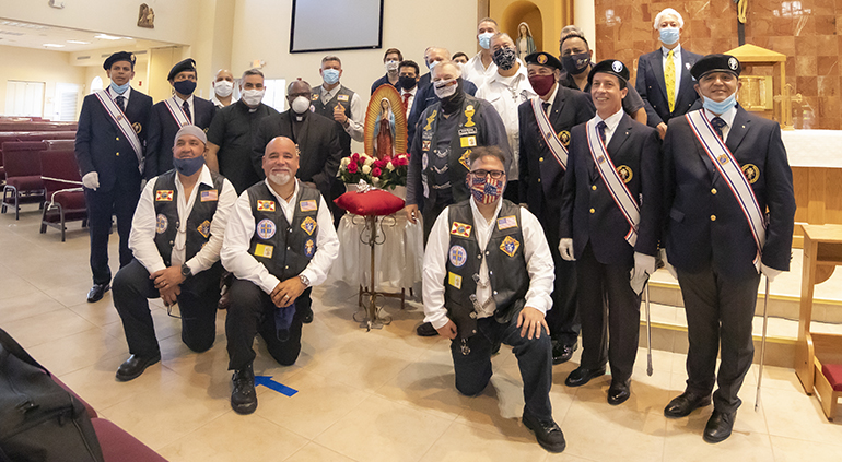 Archbishop Thomas Wenski stands next to the statue of Our Lady of Guadalupe with the Silver Rose icon, after a special prayer service July 3, 2020 at St. John XXIII Church in Miramar, marking the visit of the Silver Rose Pilgrimage through the Archdiocese of Miami. Members of the Knights of Columbus Council 14390 and members of the Knights on Bikes are gathered around the archbishop.