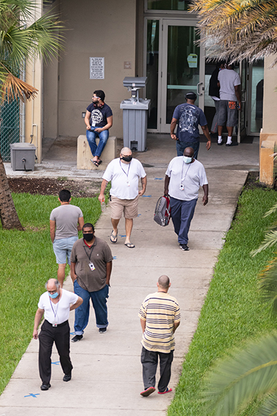 Residents, staff and guests at Miami's Camillus House shelter for the homeless in Miami move through the shelter's courtyard during a visit of the U.S. Surgeon General, Dr. Jerome Adams, July 23, 2020.
