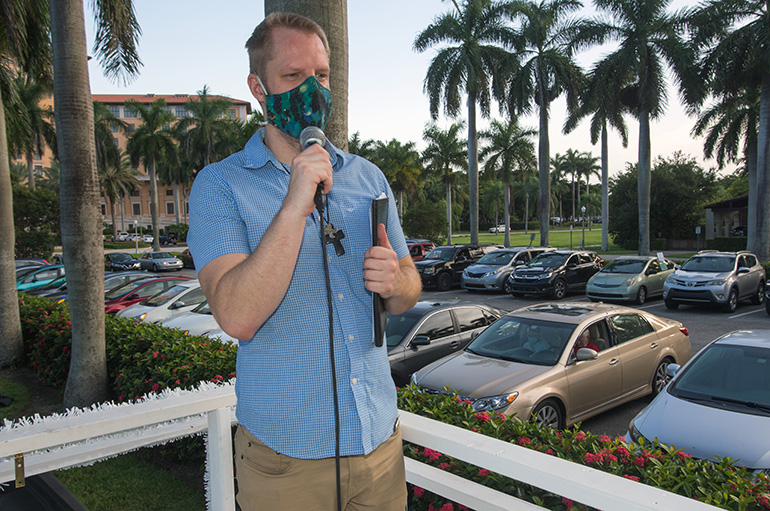 Aaron Lauer, associate pastor at Coral Gables Congregational Church, speaks to participants at PACT's drive-in rally July 27, 2020.  Cars filled the parking lot of Coral Gables Congregational and a vacant lot nearby to listen to PACT speakers who urged more funds for affordable housing and a community ID.