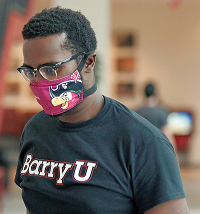 A student models the face mask, branded with Bucky the Barry University mascot, that the university will give everyone who works and studies there.