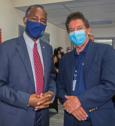 Catholic Charities Director Peter Routsis-Arroyo, right, poses for a photo with U.S. Housing and Urban Development Secretary Dr. Ben Carson during his visit to Catholic Charities' Malcolm Ross Senior Center, Aug. 13, 2020.