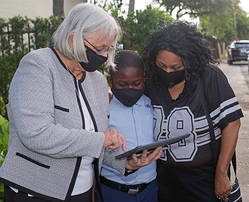 Sister Stephanie Flynn, left, St. James School principal, shows third-grader Ben Lafortune 8, and his mother, Etanya Lafortune, how to log into his class on the first day of COVID-19 induced virtual school, Aug. 19, 2020.