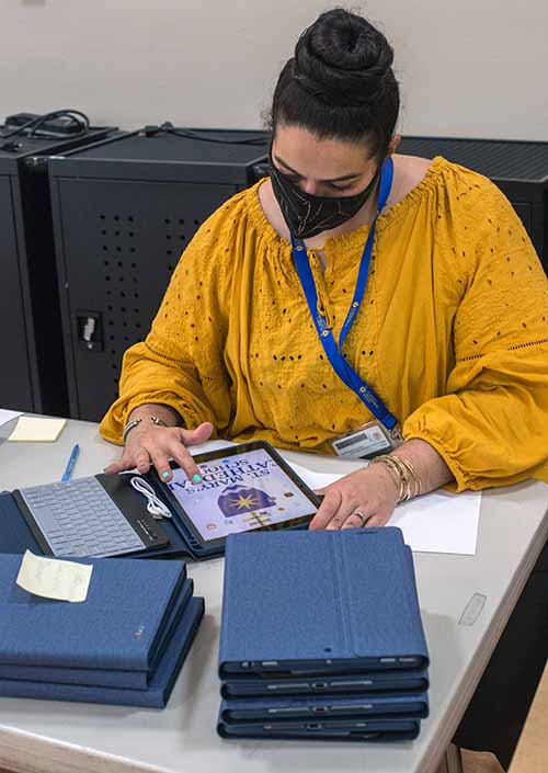 St. Mary Cathedral School's second grade teacher, Cristina Gomez-Torres, sets up iPads for students as COVID-19 induced virtual school opened, Aug. 19, 2020.
