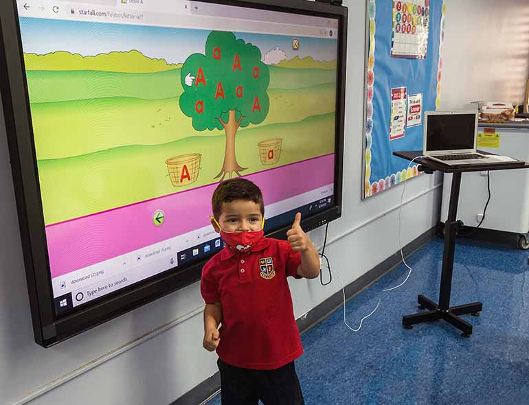 St. Hugh pre-K student Andres Valverde, 3, gives a thumbs up to smart board on the first day of school, Aug. 19, 2020. Pre-K students returned in person while K-12 students did so virtually due to the COVID-19 pandemic.