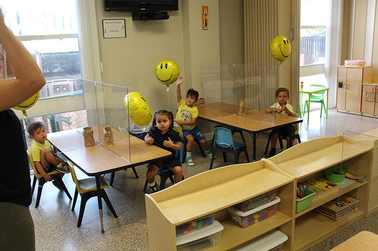 PreK3 students at Nativity School in Hollywood look past plexiglass partitions at their teacher, Brenda Bianchi,  on the first day of school, Aug. 19, 2020. PreK students were allowed to resume in-person classes at archdiocesan schools, while K-12 students returned only virtually.