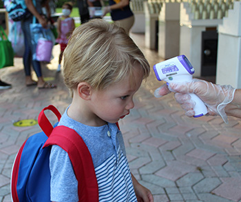 A PreK2 student has his temperature taken upon arriving at Nativity School in Hollywood on the first day of school, Aug. 19, 2020. PreK students were allowed to resume in-person classes at archdiocesan schools, while K-12 students returned only virtually.