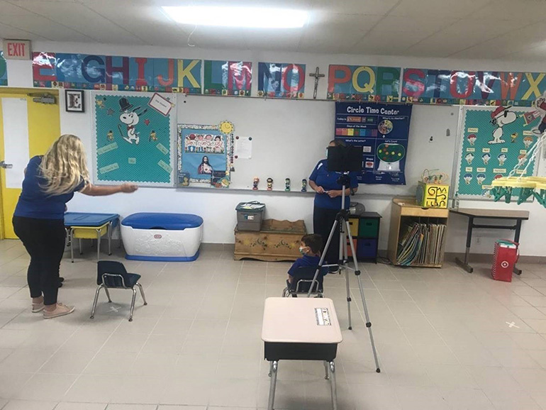 Our Lady of Lourdes School's PreK3 teacher, Nora Estrada, sets up circle time for in person instruction on the first day of school, Aug. 19, 2020. At right, an iPad is on the tripod for the virtual students.. PreK parents could choose between in-person and online instruction.