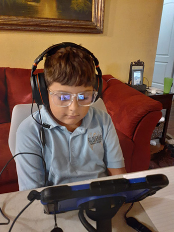 St. Michael the Archangel third grader Sabrian Fernandez is clad in his school uniform and wearing glasses to protect his eyes from the glare of the iPad as the 2020-2021 school year begins, online for now, Aug. 19, 2020.